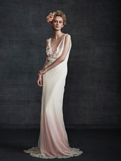 a sleeveless dip dye pink and white wedding dress with a deep neckline, draped bodice and a fabric bloom on it