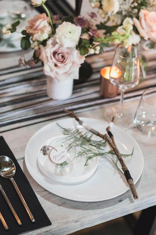 sticks, greenery and a glass ornament with greenery for decorating a winter boho wedding