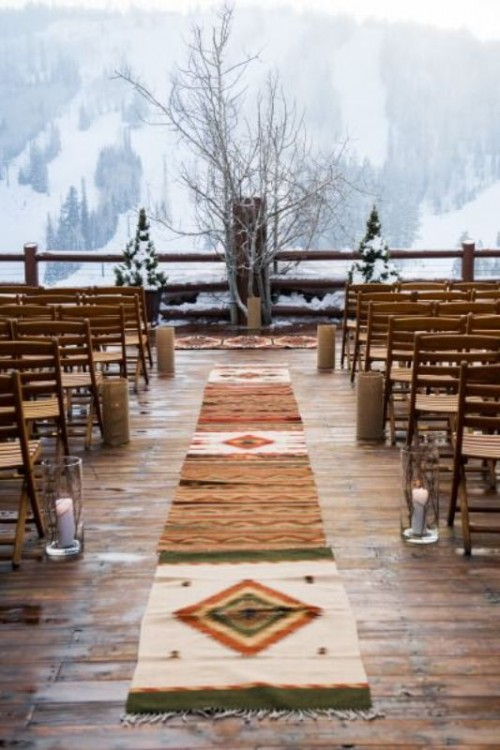 a boho winter wedding ceremony space with boho and folksy rugs, branches, snowy fir trees and candles plus a mountain view
