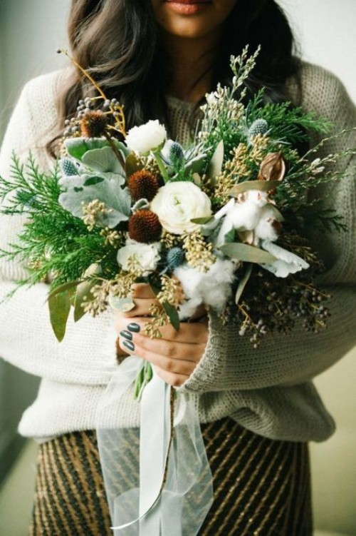 a boho winter wedding bouquet with much greenery, grasses, ferns, thistles and cotton