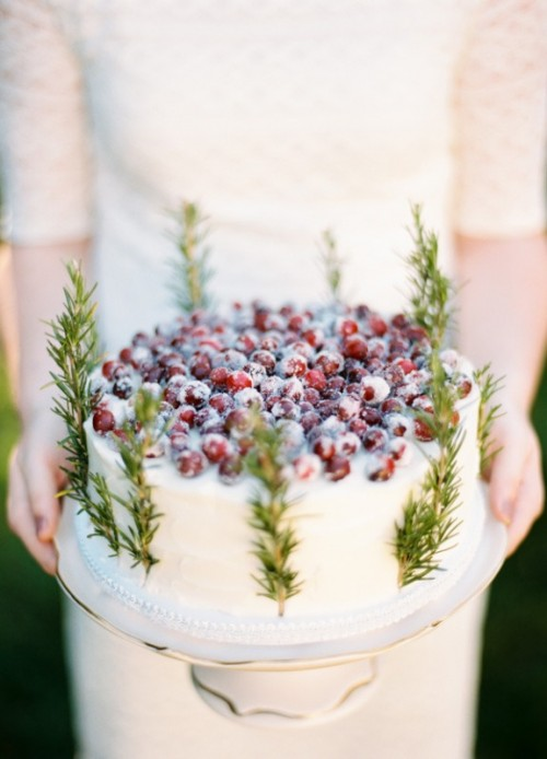 a winter boho wedding cake topped with sugared cranberries and greenery is a chic and stylish idea