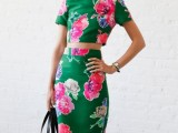 a brigth green floral two-piece dress with a crop top with short sleeves and a high neckline, a pencil skirt, a striped bag