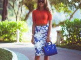 an orange crop top with short sleeves and a printed blue and white pencil skirt plus a bright blue bag and nude shoes