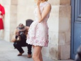 a pink floral mini dress with a high neckline and no sleeves plus white heels