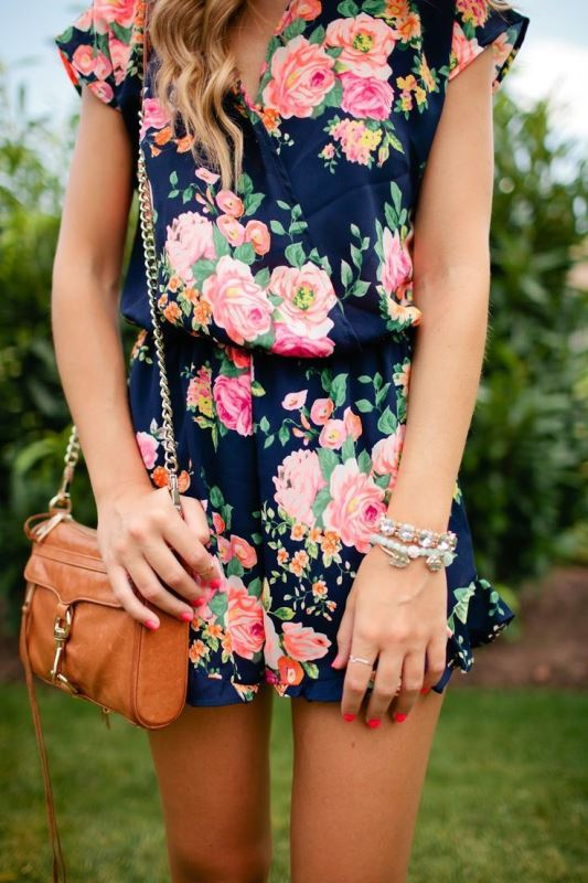 a navy romper with a bright floral print and an amber bag for a casual summer bridal shower