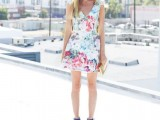 a bright floral mini dress with no sleeves and a V-neckline, bright blue shoes and a metallic clutch