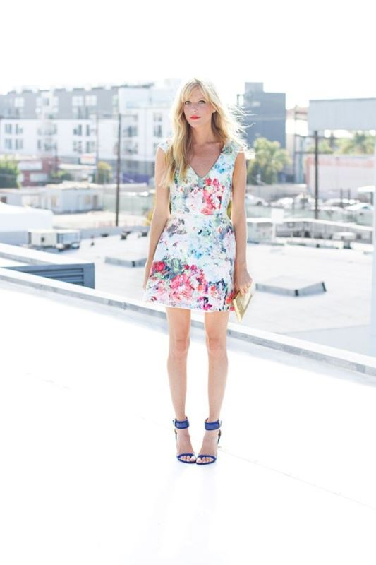 a bright floral mini dress with no sleeves and a V neckline, bright blue shoes and a metallic clutch