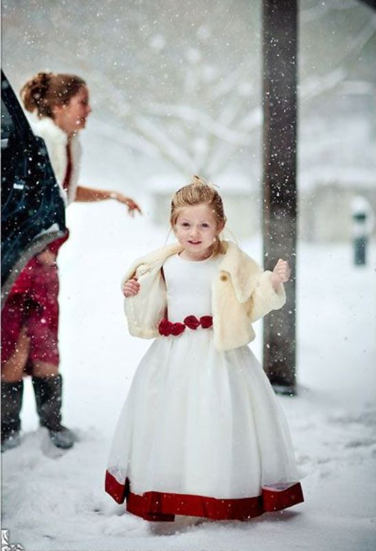 a white A line dress with red detailing, red ribbon on the edge, a neutral faux fur coverup for a winter flower girl look