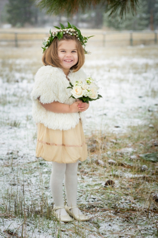 a short tan dress, a white faux fur coverup, white tights and shoes for a chic and beautiful winter flower girl look