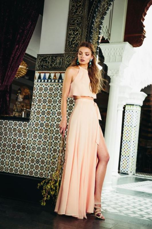 a simple look in blush with a halter neckline crop top and a maxi skirt with a slit plus strappy shoes