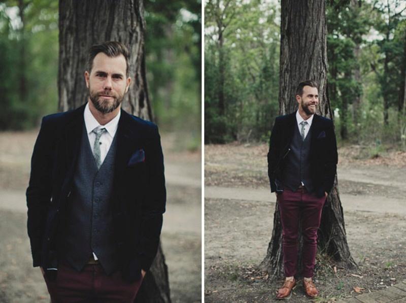 a bold groom's outfit with burgundy velvet pants, a grey waistcoat, a navy velvet blazer and a light grey tie