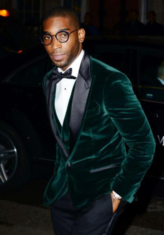 a chic fall or winter groom's outfit with a green velvet blazer with black lapels, a waistcoat, a black bow tie and pants