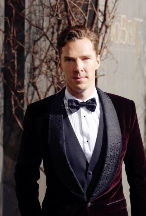 Benedict Cumberbatch wearing a burgundy velvet tuxedo with printed black lapels, a black waistcoat and a printed bow tie