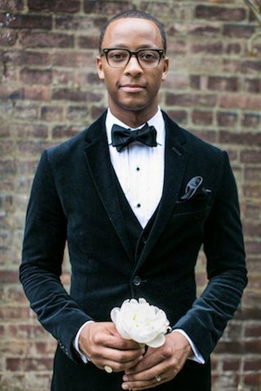 a stylish groom's outfit with a three piece dark green velvet suit and a black bow tie plus a black silk bow tie