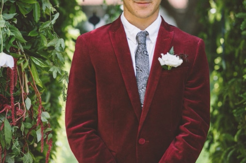 a burgundy velvet blazer with a grey printed tie is a stylish combo for a fall or winter groom's look