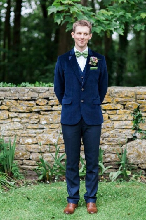 a bright blue velvet blazer, a blue polka dot waistcoat, bright blue pants, brown shoes and a green bow tie