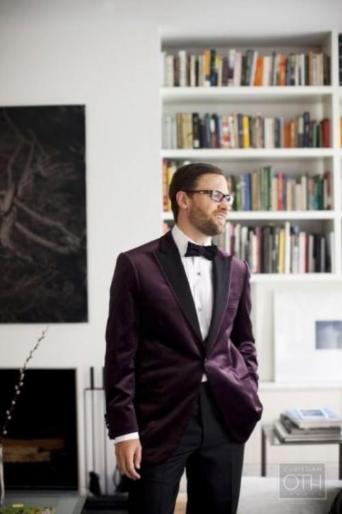 a purple velvet tuxedo with black lapels, black pants and a bow tie for a chic and bold fall or winter groom