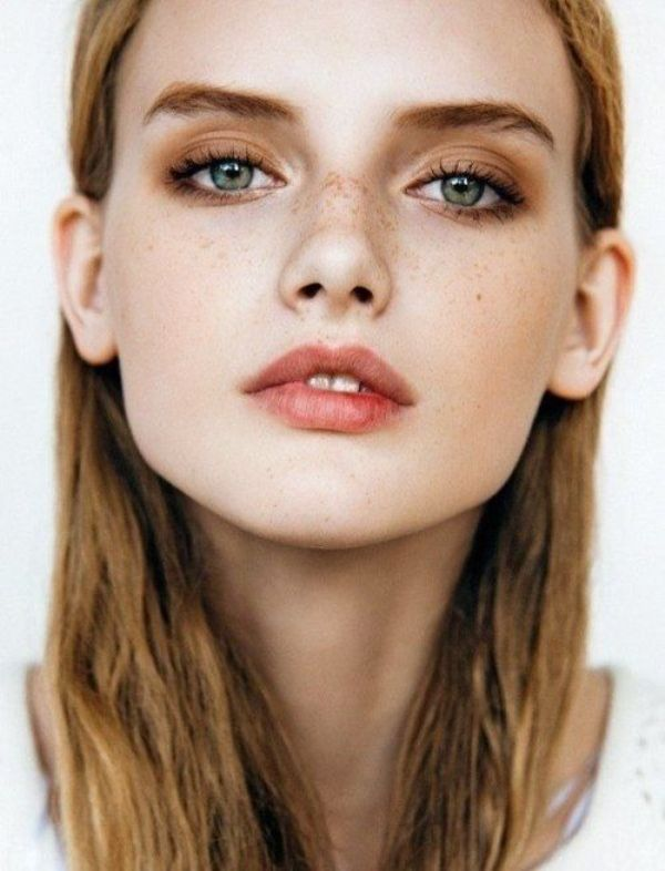 a nude style makeup with a matte pink lip, brown smokeys, fresh and shiny skin and accented green eyes