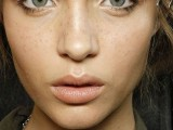 a nude makeup with a glossy nude lip, slight smokeys, accented eyebrows and highlighted skin