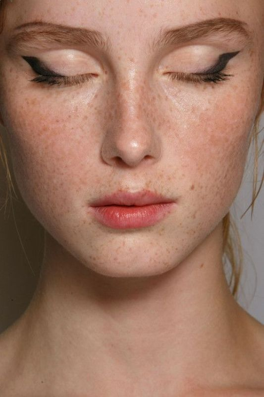 a creative makeup with a kiss effect pink lip, eyeliner and accented eyebrows plus shiny and highlighted skin