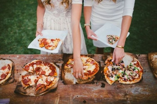 a rustic pizza bar with a wooden board, pizzas on plates and chargers and some plates next to them
