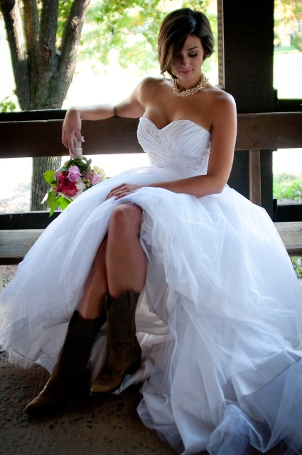 a strapless princess-style wedding dress with a draped and embellished bodice and a full skirt, brown cowboy boots is an amazing idea to rock