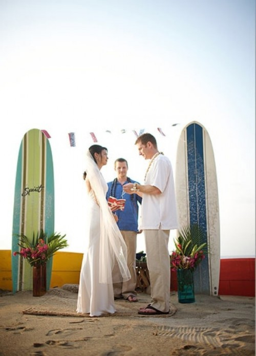 a creative tropical wedding altar of surf boards and bright blooms and greenery in jars is a cool option