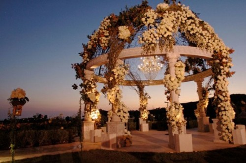 a super lush floral wedding altar with white blooms, vines, lights and a statement crystal chandelier