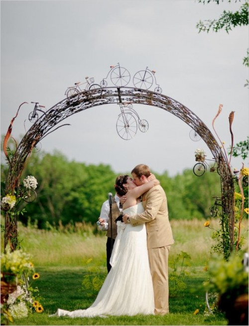a vine wedding arch with sunflowers and neutral blooms and vine bikes for a bike-loving couple