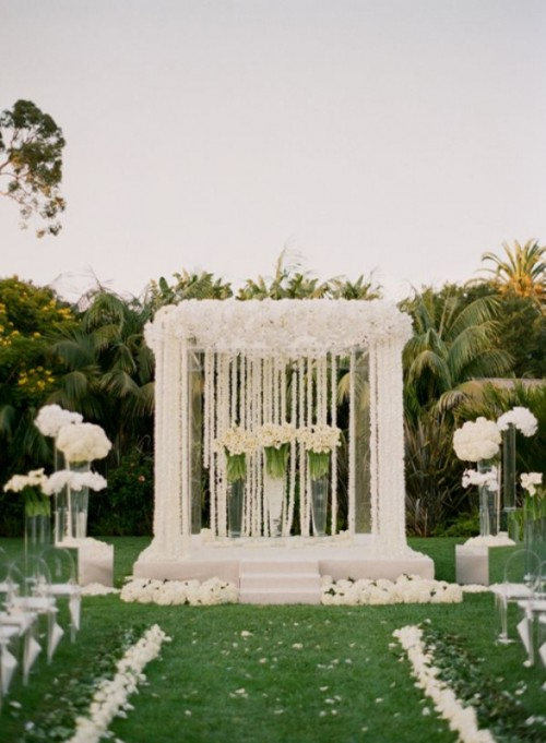 a refined wedding altar with white blooms and petals all over it, white floral arrangements in sheer acrylic vases and on stands seem floating in mid-air