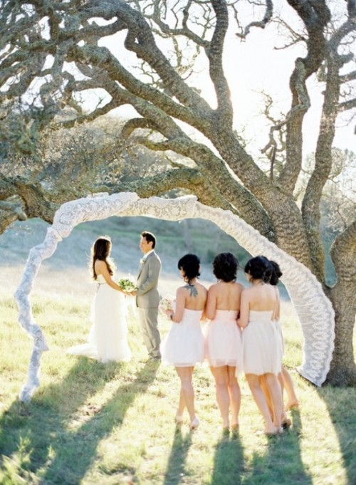 an arch of a living tree fully covered with white lace is a cool wedding decoration