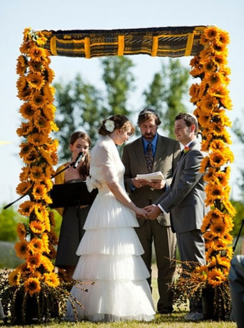 a unique wedding arch covered with sunflowers and with some bright fabric on top is a cool wedding altar for a rustic wedding
