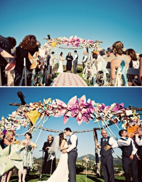 a wedding arch fully decorated with large and colorful paper flowers is a cool idea for a bright wedding