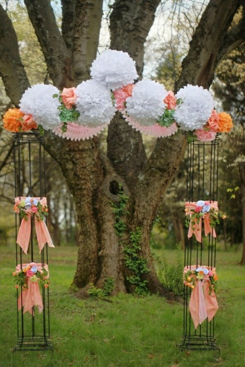 a unique wedding altar with paper pompoms and blooms on top and pillars with ribbons bows and bright blooms
