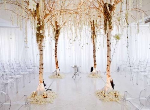 a unique wedding altar of birch trees, blooms and greenery hanging down, white petals and candles
