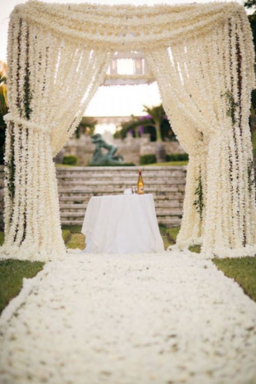 a super lush white floral altar and the aisle fully covered with white flower petals are a wedding ceremony setup