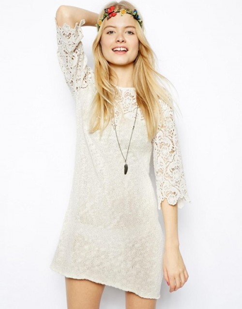 a boho lace off-white mini dress with a high neckline, short sleeves, a necklace and a floral crown for a boho bride