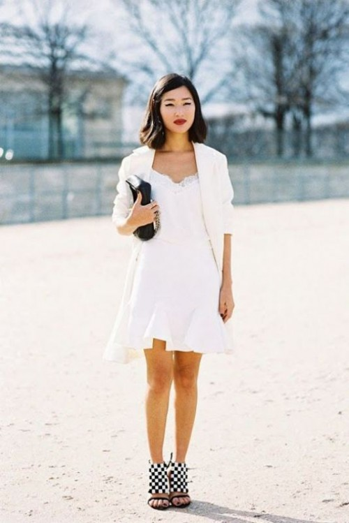 a white A-line mini dress with a lace neckline and ruffle skirt, white oversized blazer and checked shoes plus a black bag