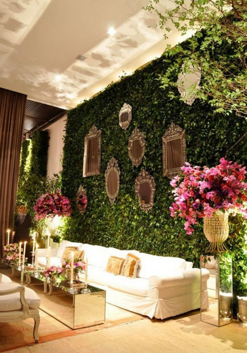 a greenery wall with mirrors in frames, bold blooms and some additional greenery around to create a refined and fresh lounge at the wedding