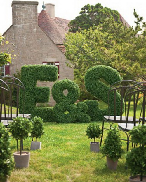 a fun garden wedding backdrop of moss letters and an ampersand plus potted greenery along the aisle for a very cool and modern look