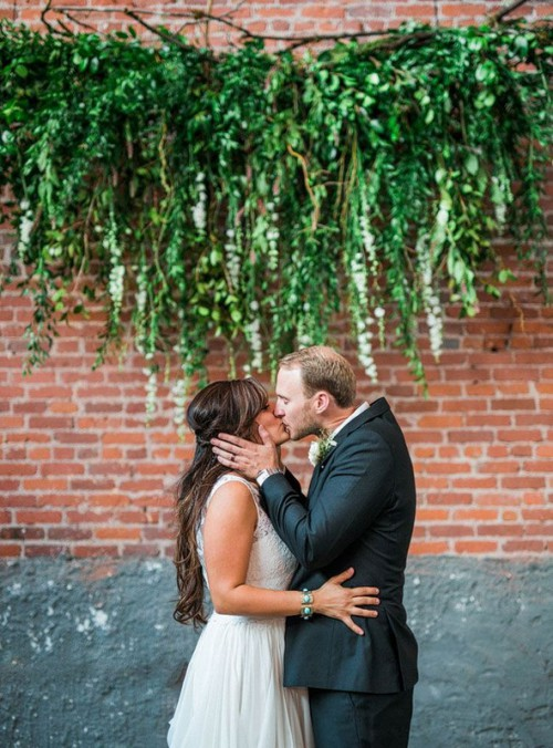 an exposed brick wall is softened with a greenery hanging and looks as a fresh and wild wedding backdrop