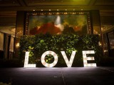 a tropical greenery backdrop with oversized shining LOVE letters is a great idea both for a ceremony and a reception space