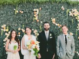 a greenery wall with some bright blooms attached is a very actual backdrop for a garden wedding