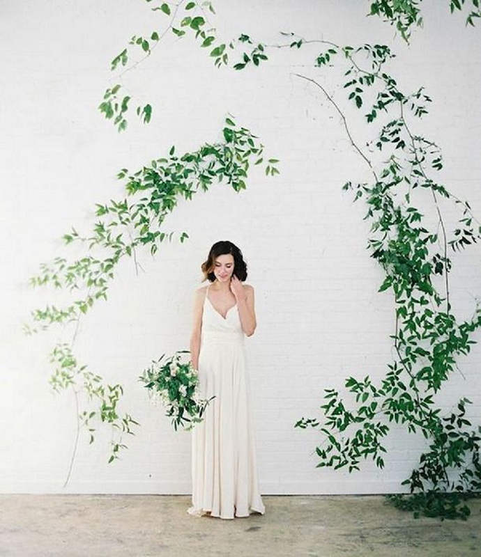 a white brick wall and some greenery on it will create an airy and light filled backdrop for your wedding ceremony