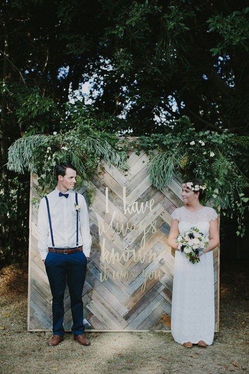 a reclaimed woodchevron wall with lush greenery with various textures is a lovely rustic backdrop for a wedding