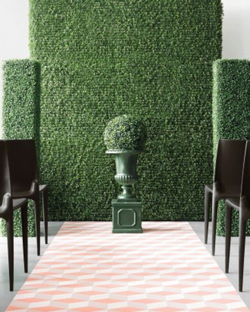 a greenery wall, a couple of pillars and a greenery ball in a vase for a refined wedding ceremony, to bring a garden feel indoors