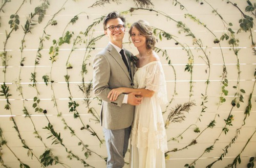 a white plank wall decorated with various foliage attached to it in circles is a lovely and whimsical wedding backdrop for a natural wedding