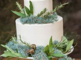 a beautiful wedding cake in white, with gorgeous greenery, branches and even dried elements for a winter or Christmas wedding
