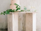 a tender blush wedding cake decorated with greenery for a spring or summer wedding
