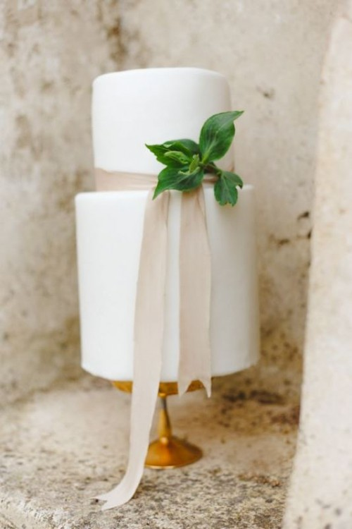 a stylish white wedding cake with neutral ribbon and some greenery for a modern or minimalist wedding